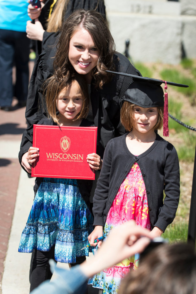 adult student in her cap and gown with two kids on graduation day