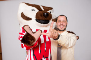 "Gabriel Neves holding up ""W"" sign with Bucky Badger"